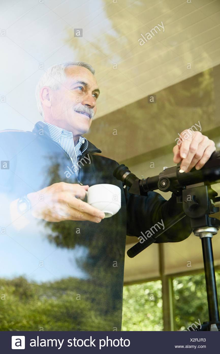 Senior man at home, drinking coffee, using telescope through window - Stock Image