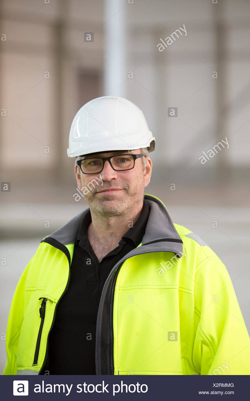 Sweden, Portrait of engineer in helmet and reflective clothing - Stock Image