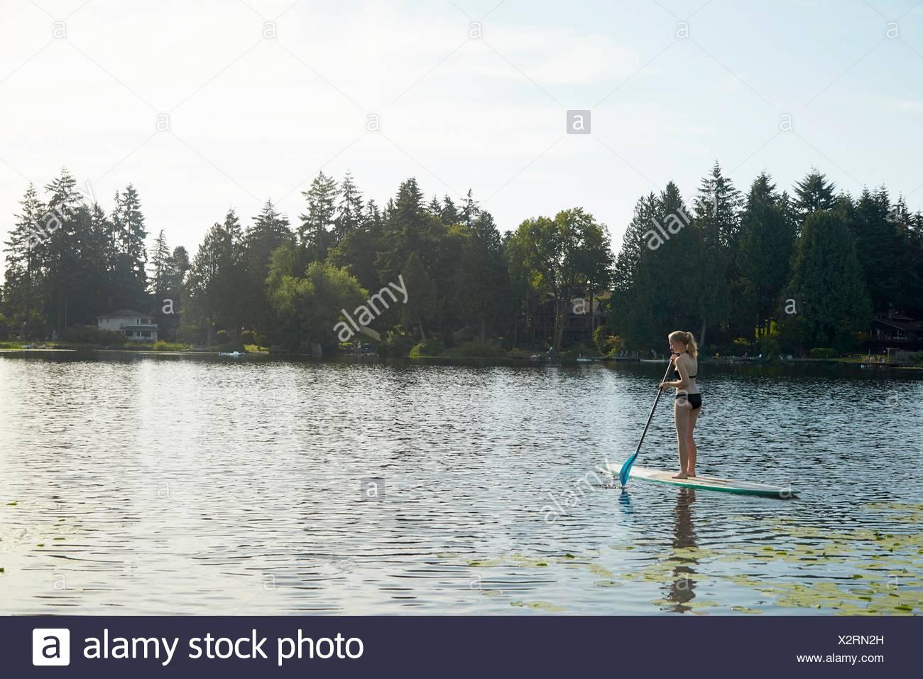Girl paddling boat in lake, Seattle, Washington, USA - Stock Image