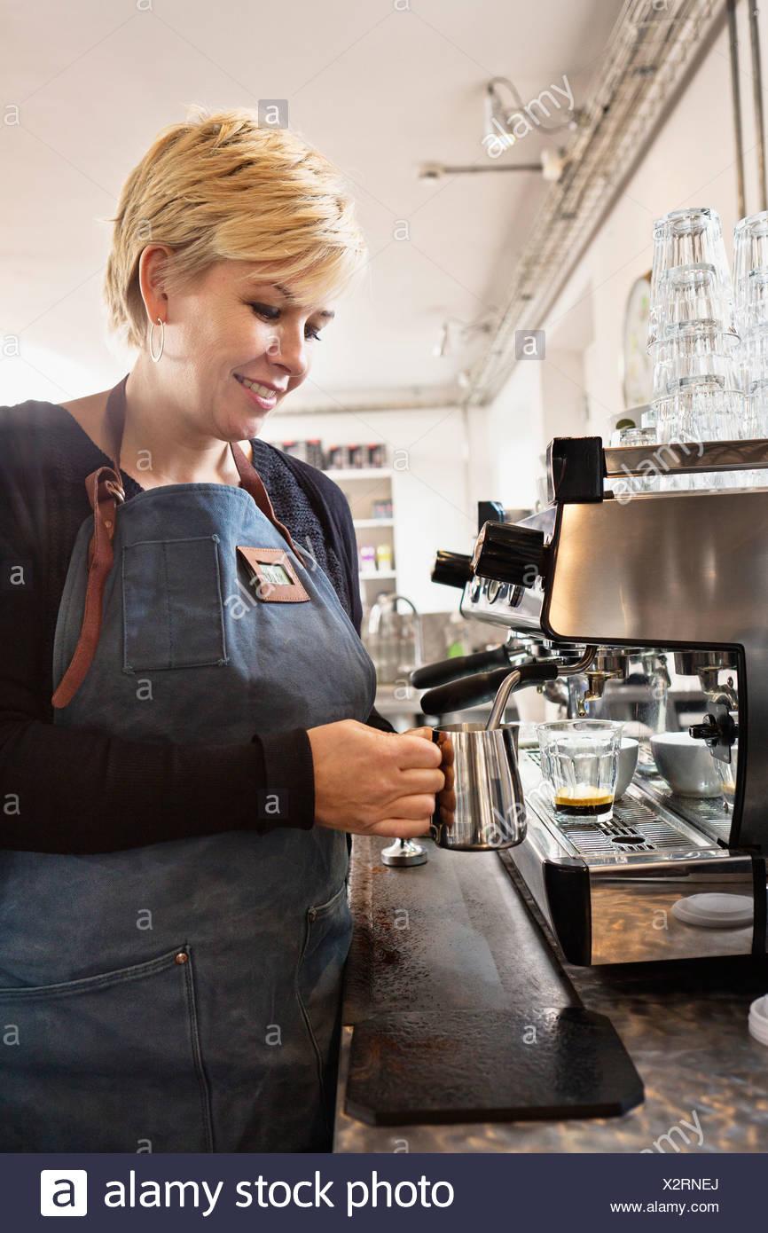 Barista heating up milk using coffee machine - Stock Image
