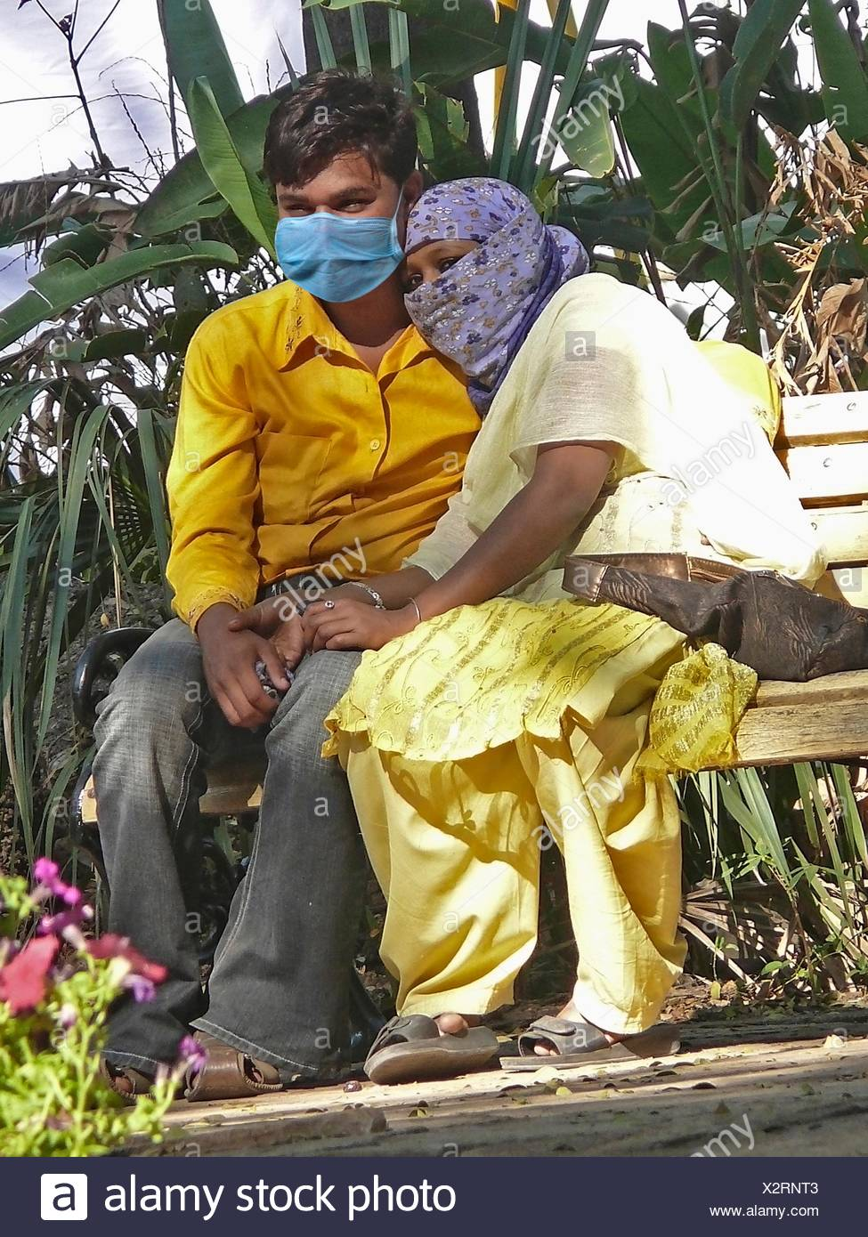 Young couple in a garden with Precaution mask for Swine Flu, H1N1 - Stock Image