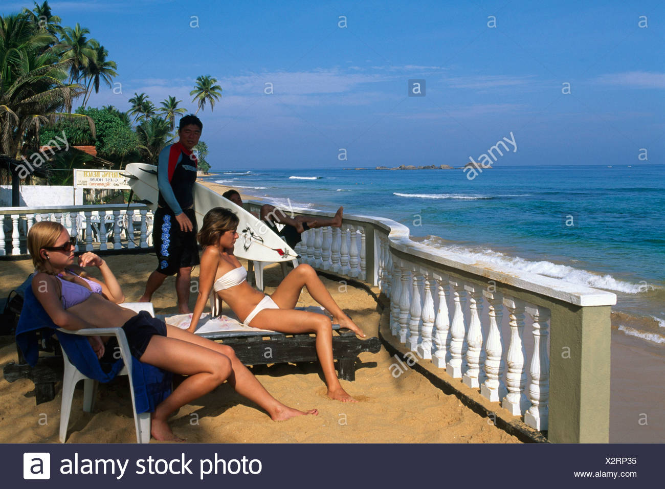 Surfers and sunbathers at Wewala Beach, Sri Lanka, South Asia - Stock Image