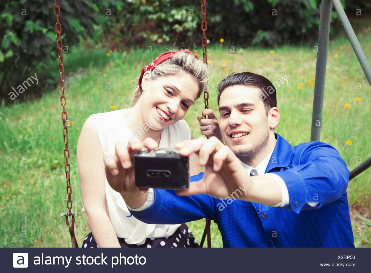 Young vintage couple taking selfie camera in garden Stock Photo