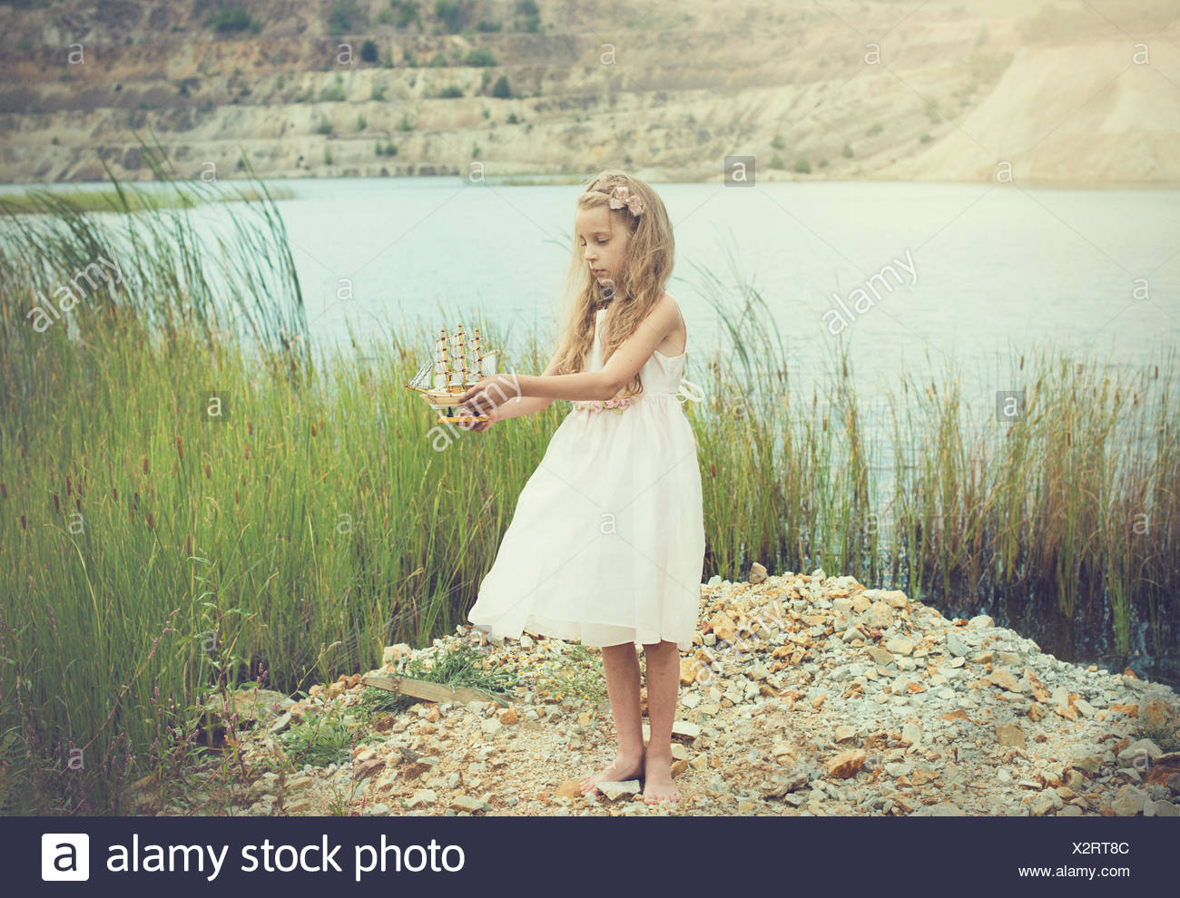 Girl standing by a lake holding a model of a boat - Stock Image