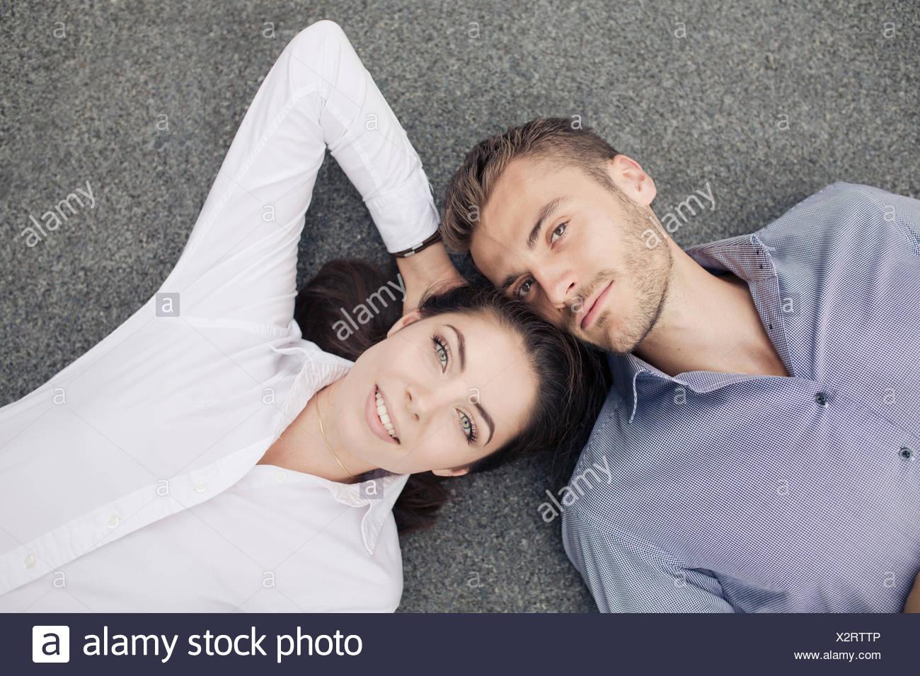 Young couple lying on floor, portrait - Stock Image