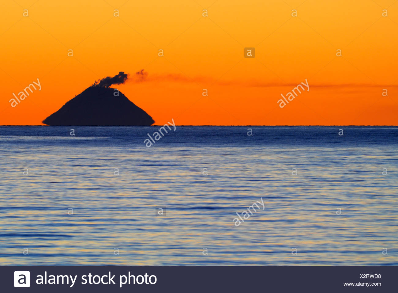 Smoke coming from Mt. Augustine Volcano (Ring of Fire) at sunset, picture taken from ca 140 km away, Kenai Peninsula, Alaska, U - Stock Image
