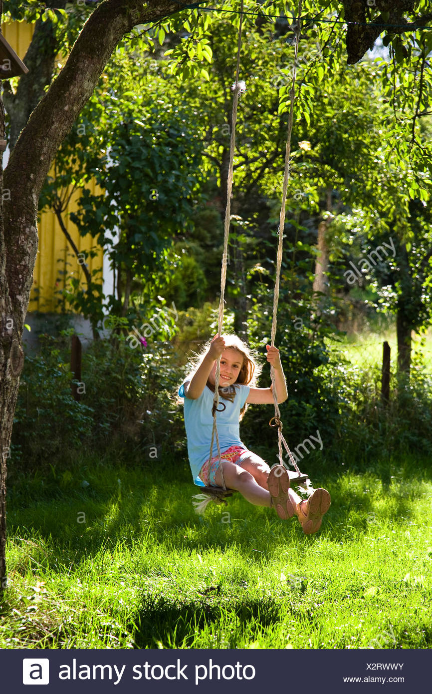 girl on a swing in the garden hung up at a tree, Sweden - Stock Image