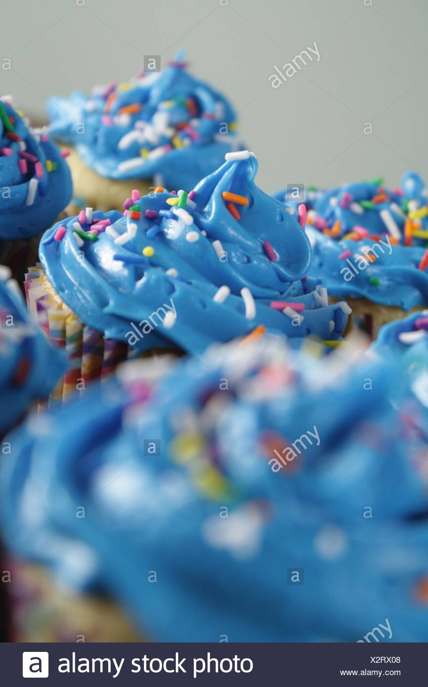 Blue Frosted Cupcakes. A grouping of cupcakes with blue frosting and sprinkles. - Stock Image