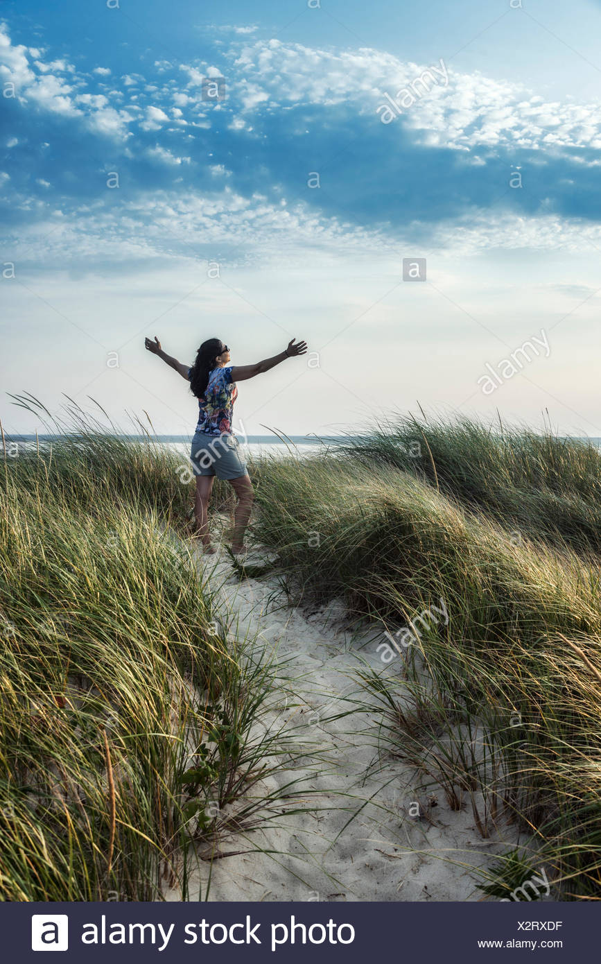 Woman rejuvenated by the coastal outdoors of Cape Cod, Massachusetts, USA - Stock Image