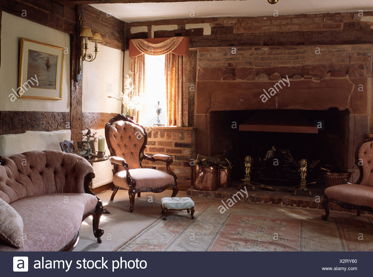 pink victorian chair and sofa in country cottage living room with