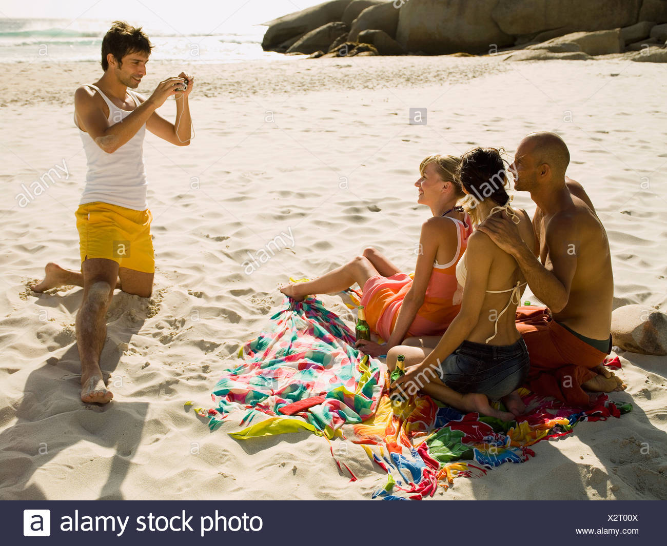 Man photographing his friends on the beach - Stock Image