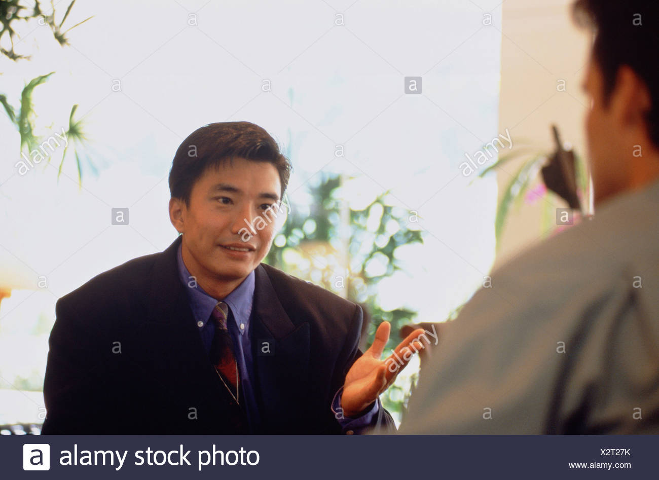 Close-up of Chinese business executive man talking with a European man on restaurant  terrace. Stock Photo