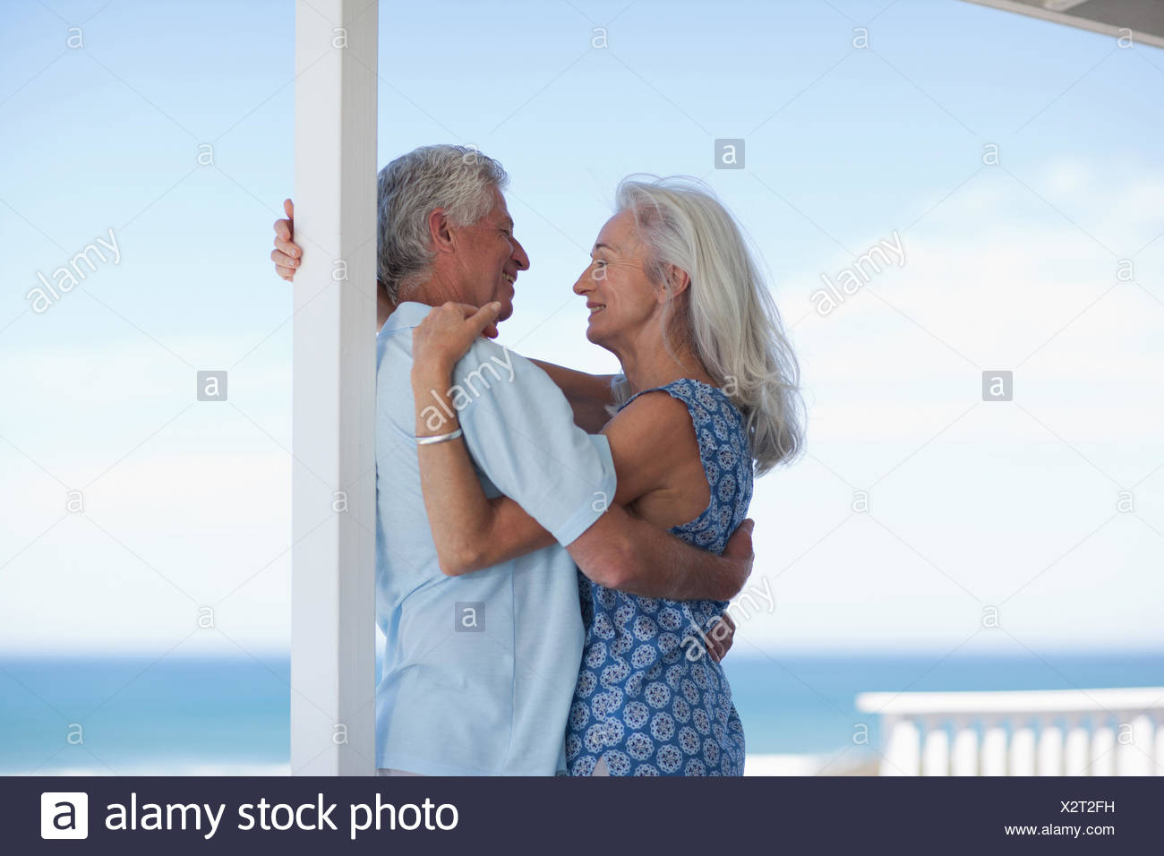 Senior couple hugging on patio and looking at ocean - Stock Image