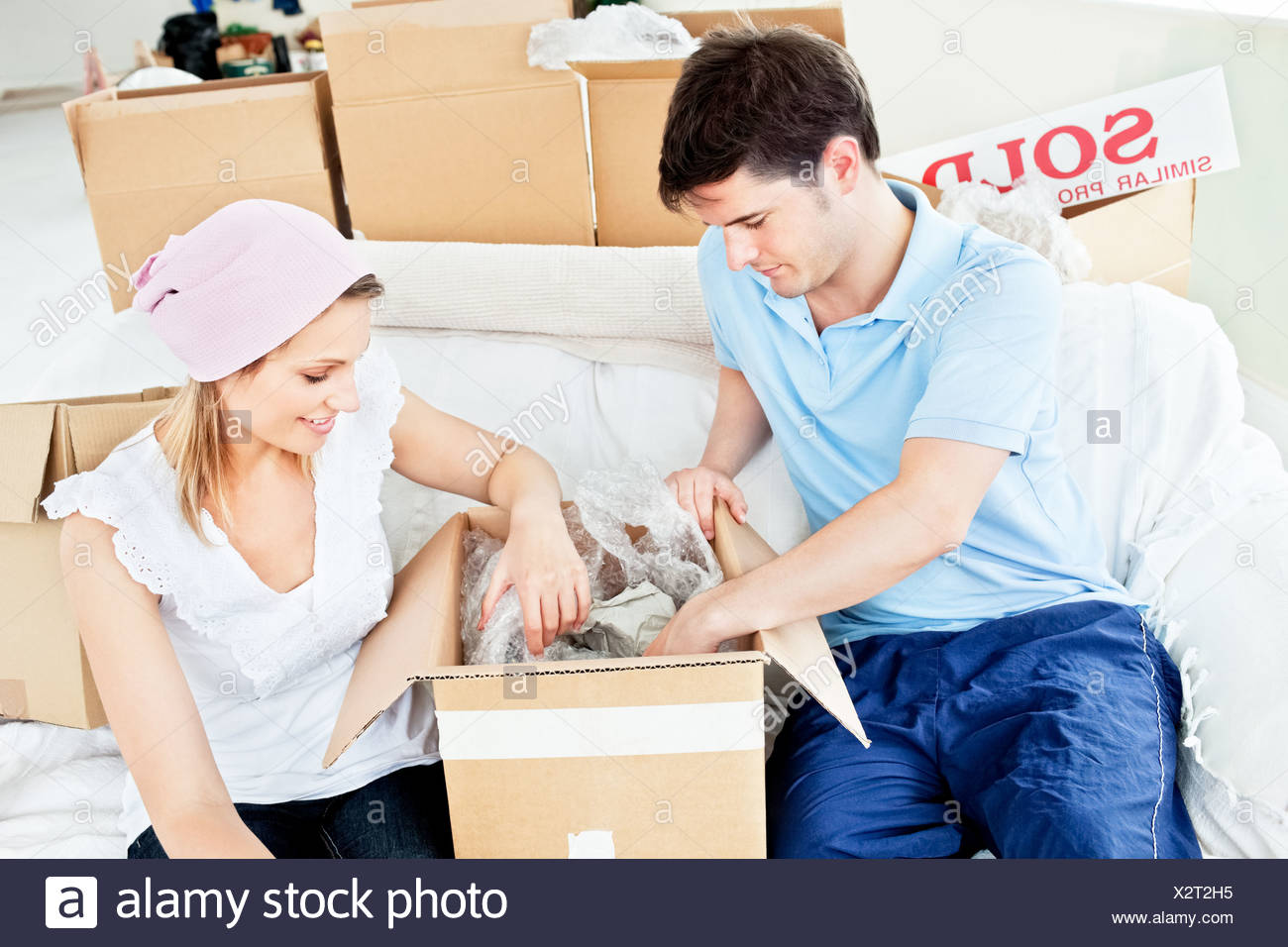 Positive young couple unpacking boxes with glasses - Stock Image
