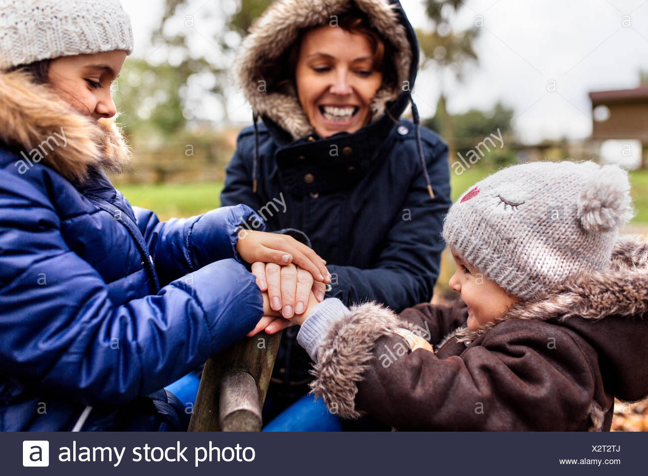 Two little sisters with her mother on a playground in autumn - Stock Image