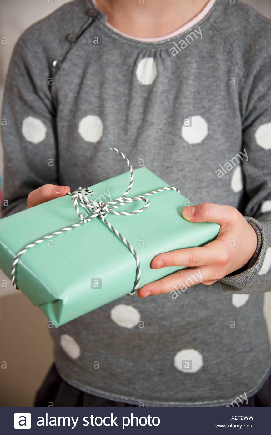 Girl on birthday party holding a gift box, Munich, Bavaria, Germany - Stock Image