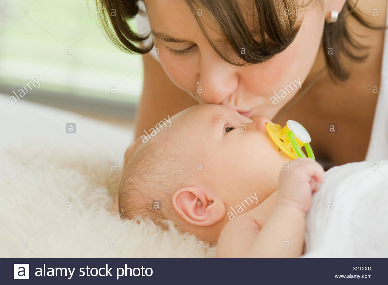 Mother kissing baby tenderly on forehead - Stock Image