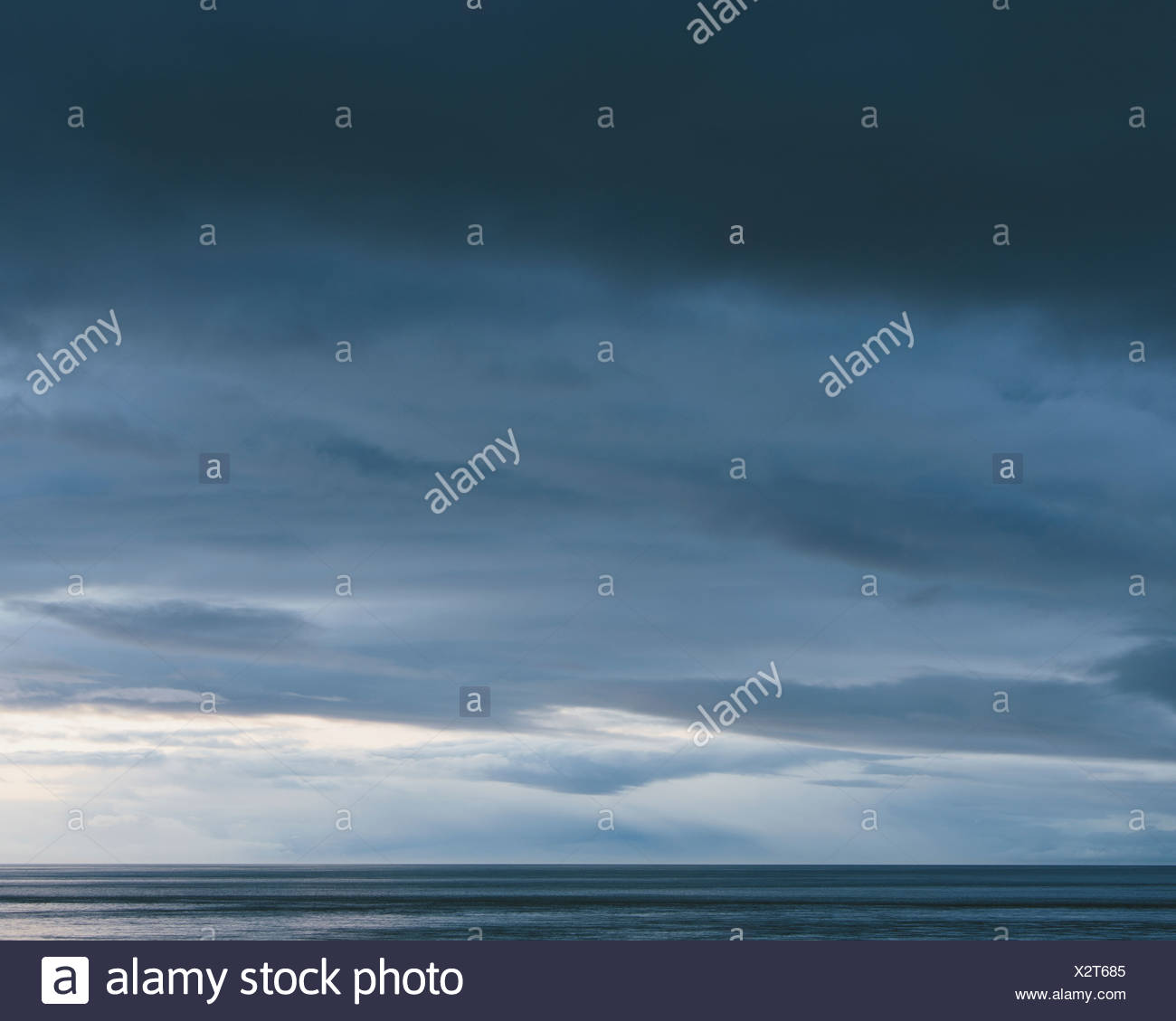 The sea and sky over Puget Sound in Washington USA The horizon with light and cloud layers above Gathering storm clouds - Stock Image