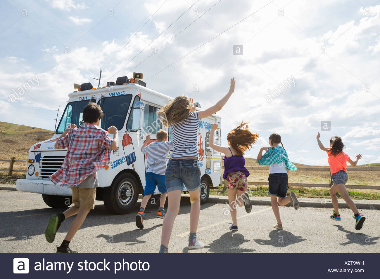Group of children running towards ice cream truck Stock Photo