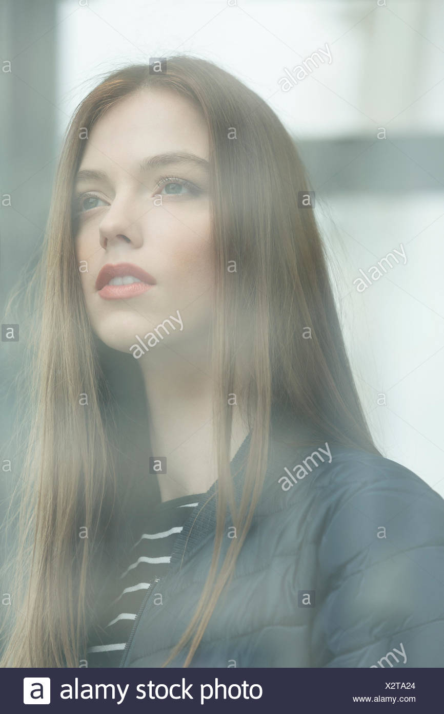 Portrait of young woman looking through window - Stock Image