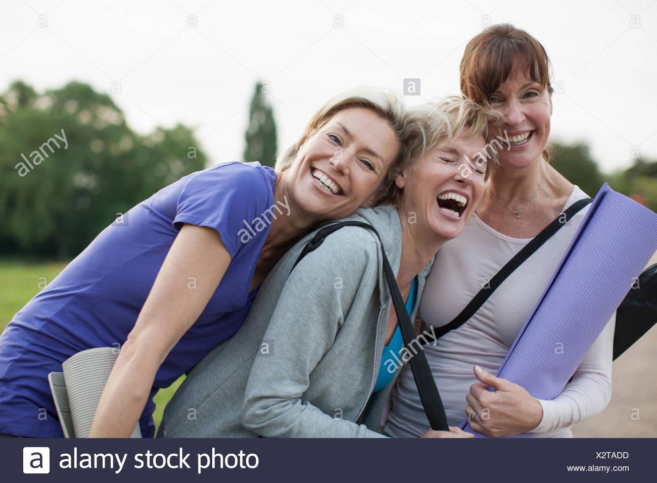 Smiling women holding yoga mats - Stock Image