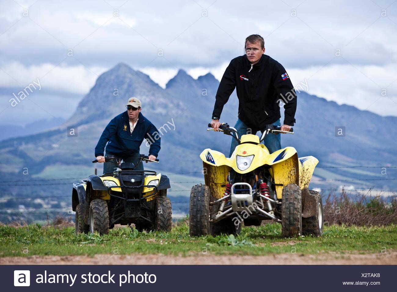 Men pause for rest on quadbikes in rural Stellenbosh - Stock Image