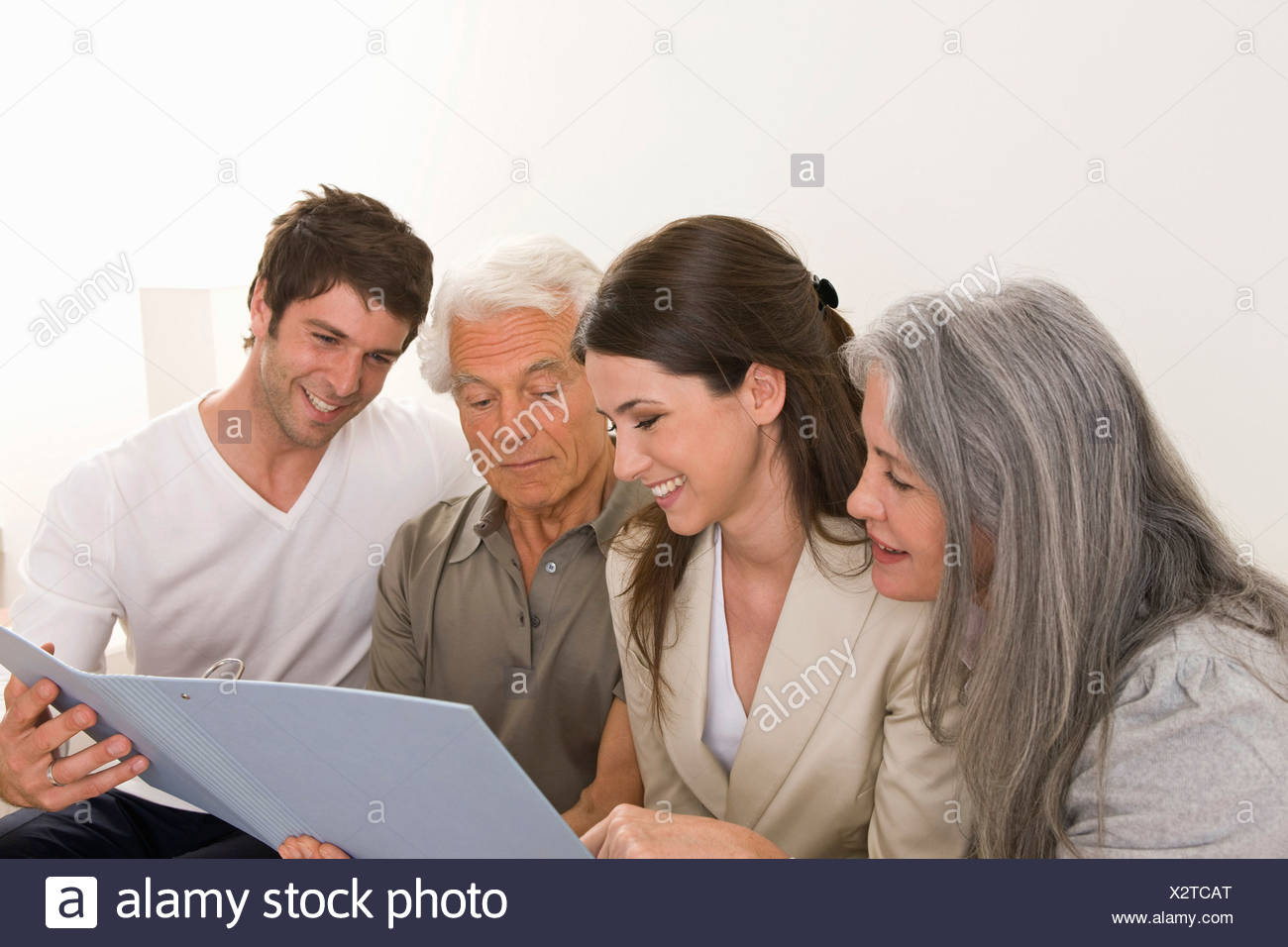 Family with adult offspring at home looking at folder - Stock Image