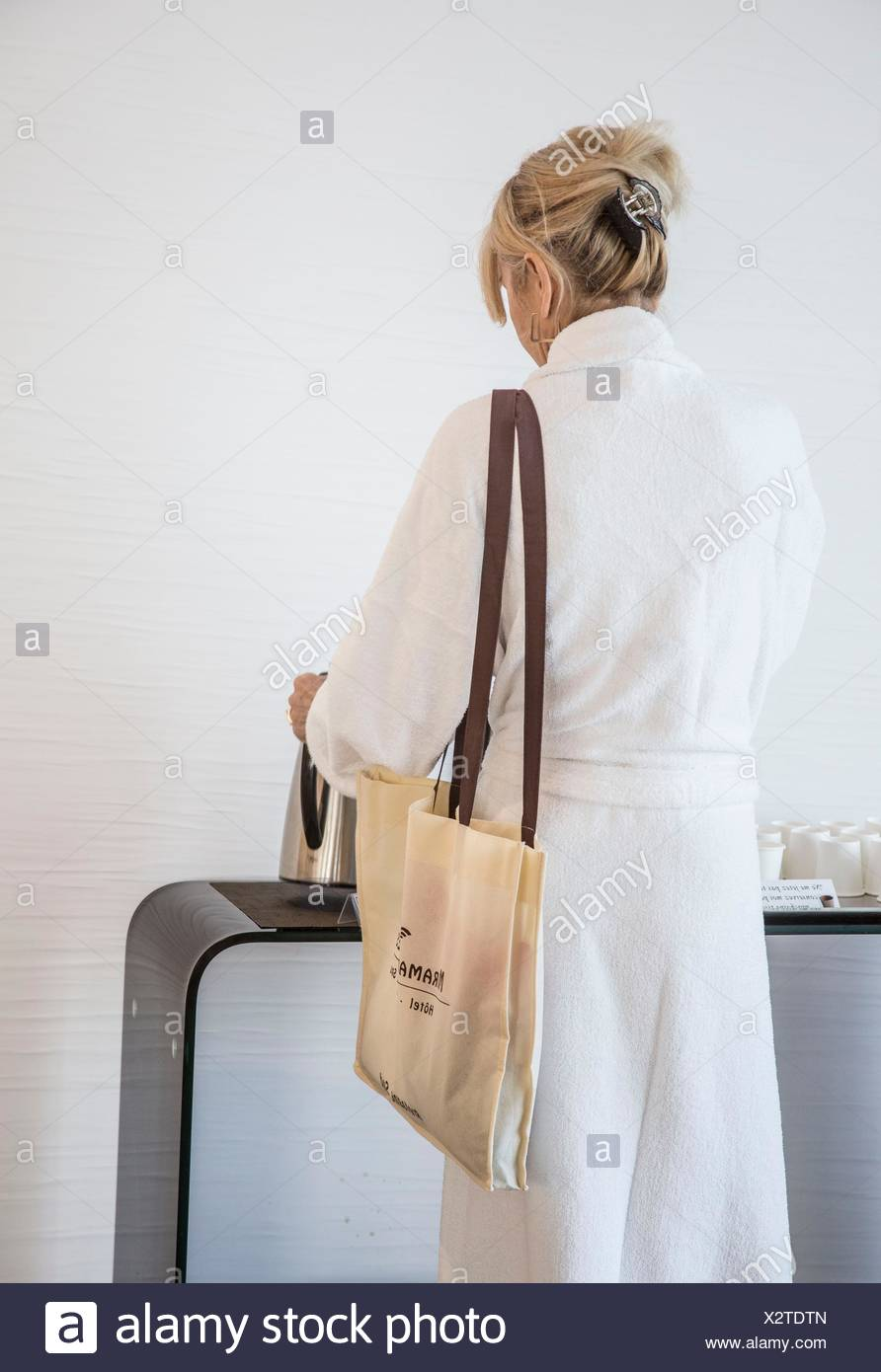 Caucasian blond woman in her spa robe in her 30´s, 40´s, 50´s with her hair tied up and getting tea between treatment. Stock Photo