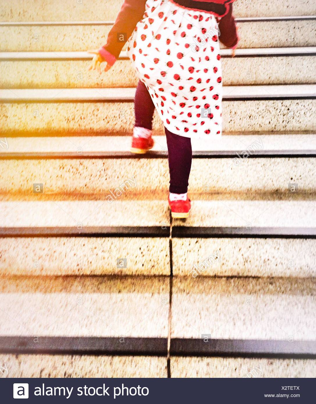 Low Section Rear View Of Girl Climbing Steps - Stock Image