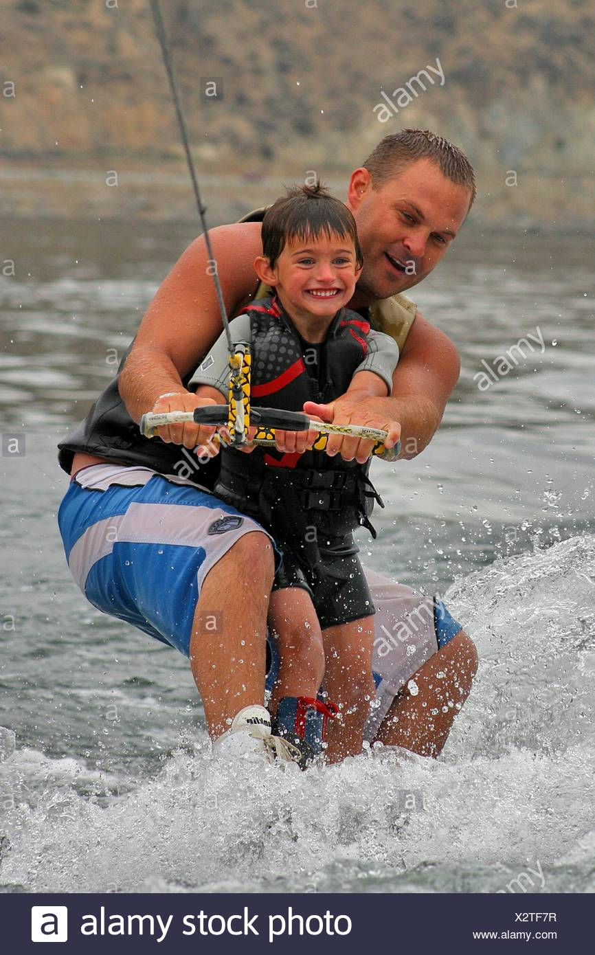 Father And Son Wakeboarding On Sea - Stock Image