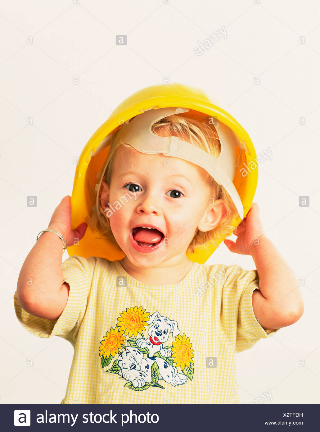 735fbe563 Indoor studio portrait of child trying on yellow hard hat Stock ...
