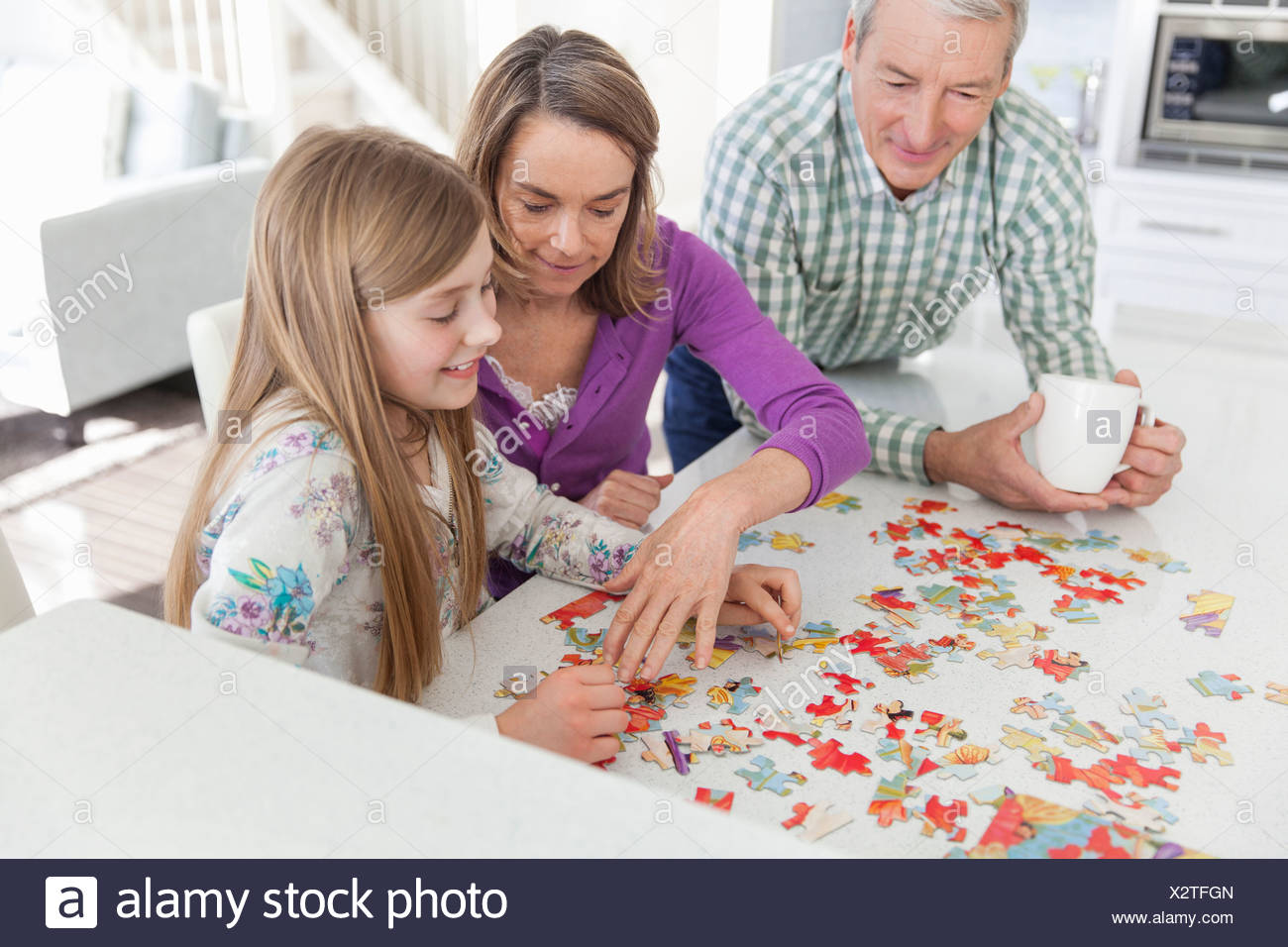 Granddaughter doing jigsaw puzzle with grandparents in kitchen - Stock Image
