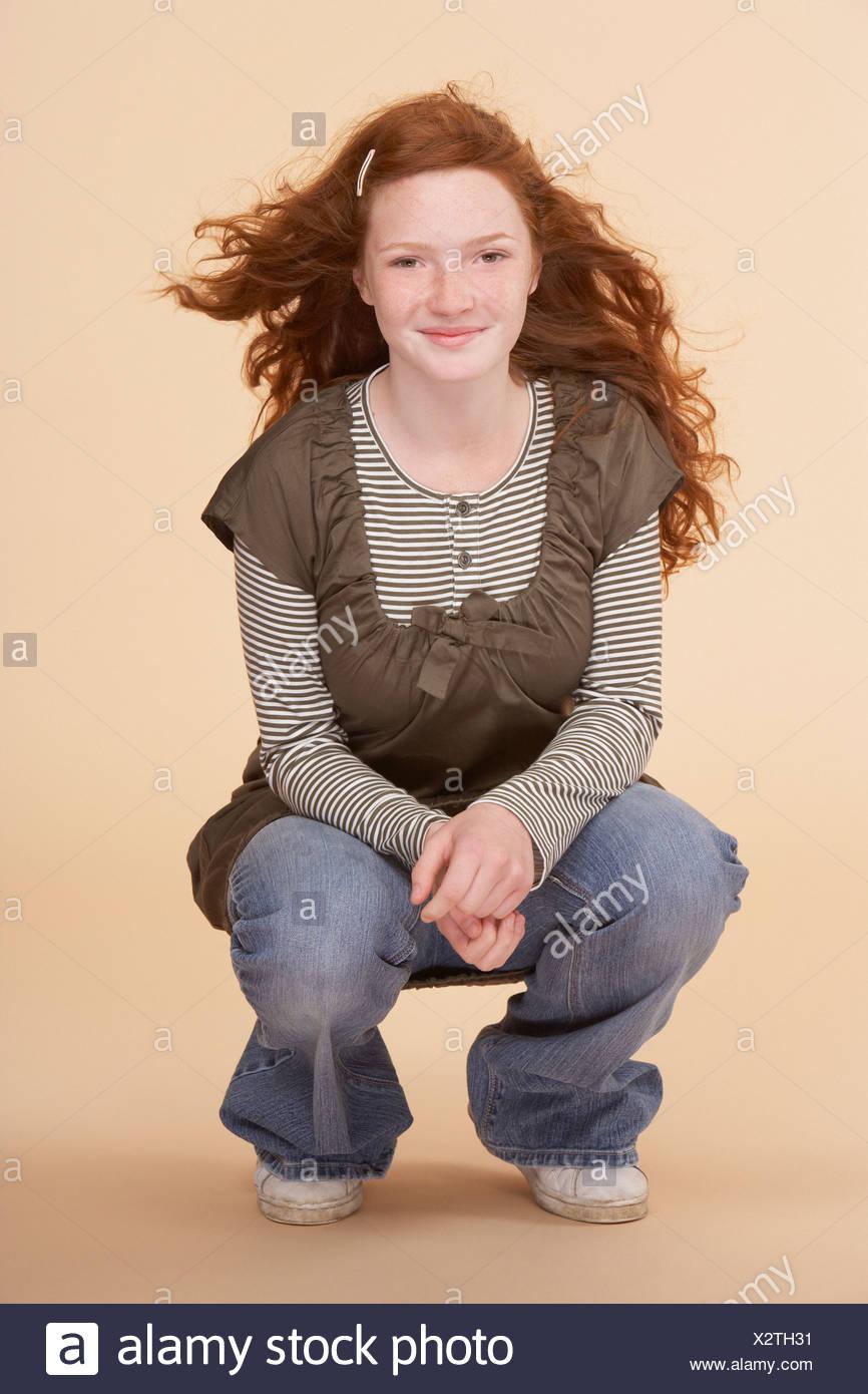 Young girl crouching on floor indoors - Stock Image
