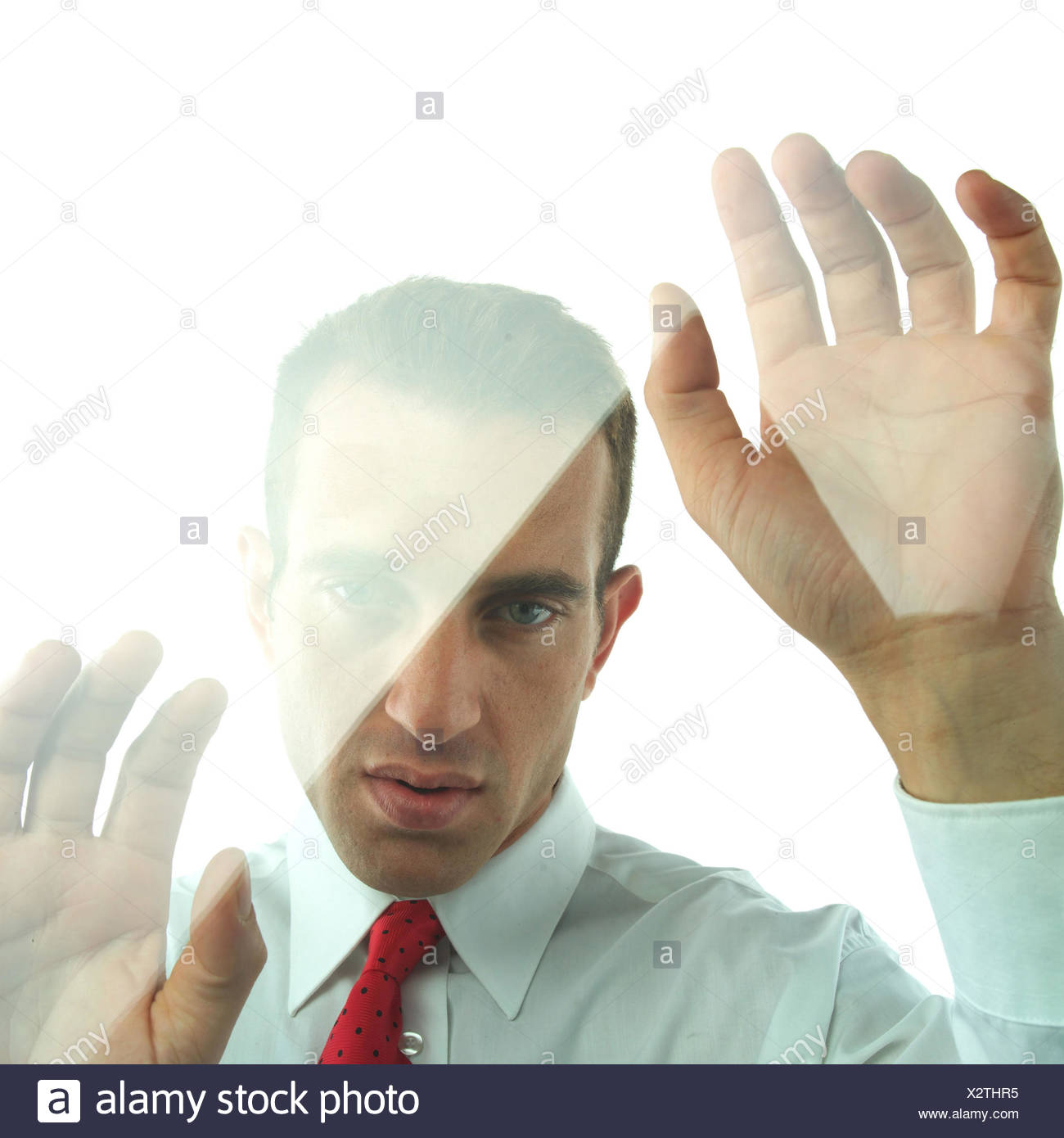 Man, gesture, windowpane, portrait, model released, very close, mood, expression, seriously, thoughtful, thoughtfulness, melancholy, melancholia, sadness, sadly, loneliness, lonely, isolates, isolation, hands, slice, surprises, in bewilderment, bewilderment, confused - Stock Image