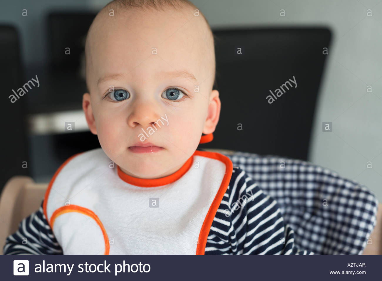 Portrait of staring baby boy in high chair - Stock Image