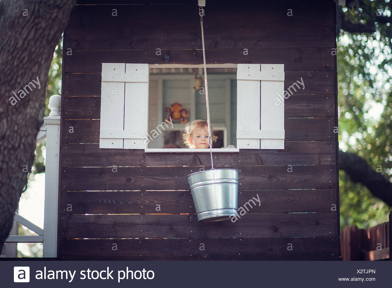 Boy in tree house looking out of the window - Stock Image