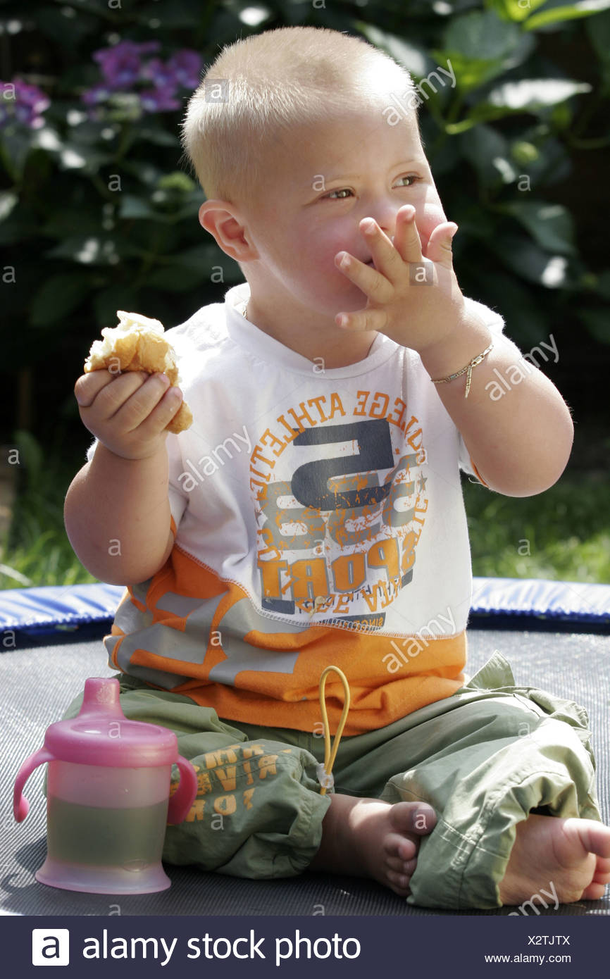 Down syndrome baby boy genetic disorder child eating bread with hands outside. - Stock Image