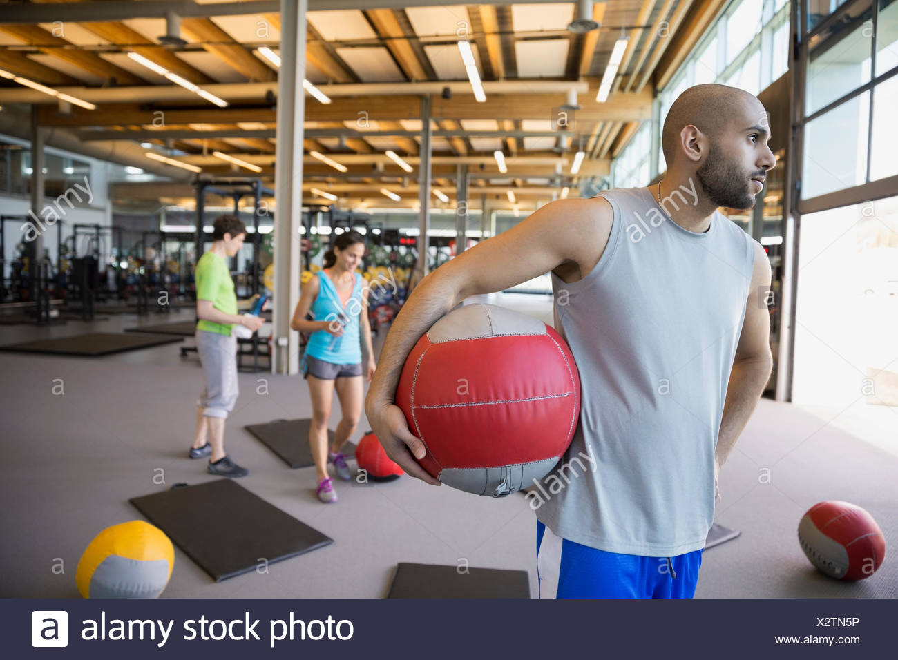 Pensive man holding medicine ball in exercise class - Stock Image