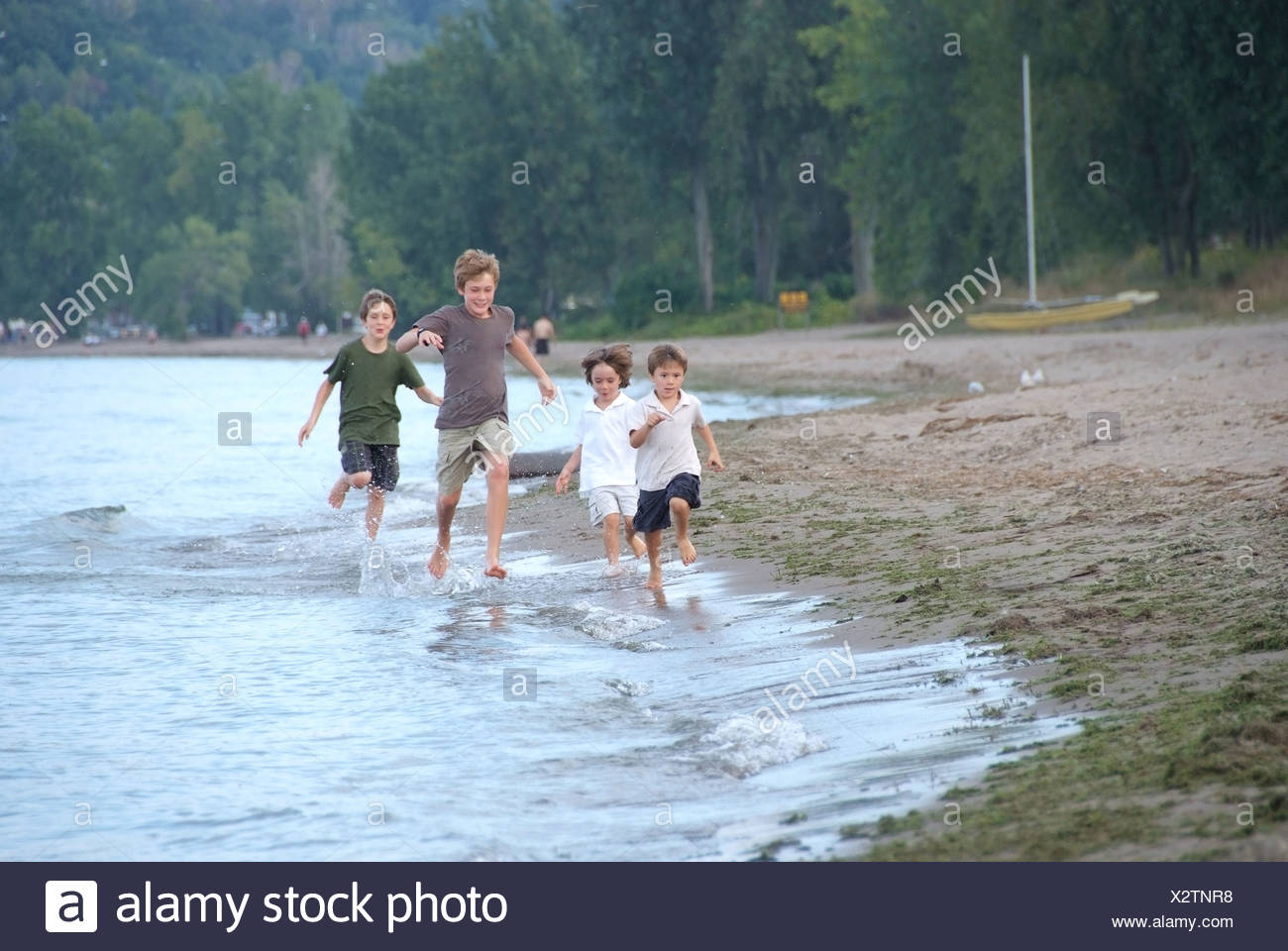 Four brothers racing along shore of Lake Erie, Turkey Point Beach, near Simcoe, Ontario - Stock Image