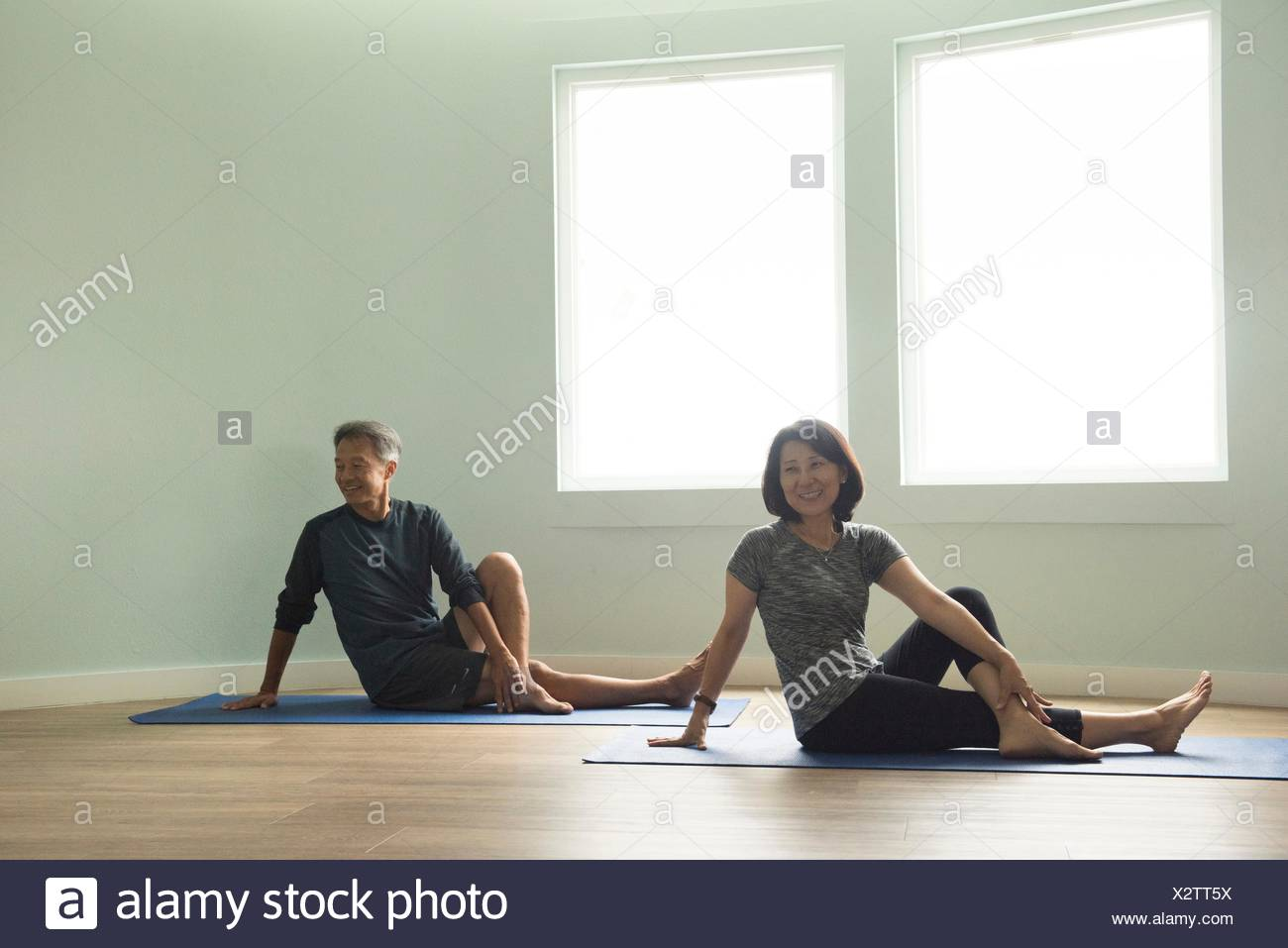 Mature couple sitting on yoga mat leaning on hand, legs crossed looking away smiling - Stock Image