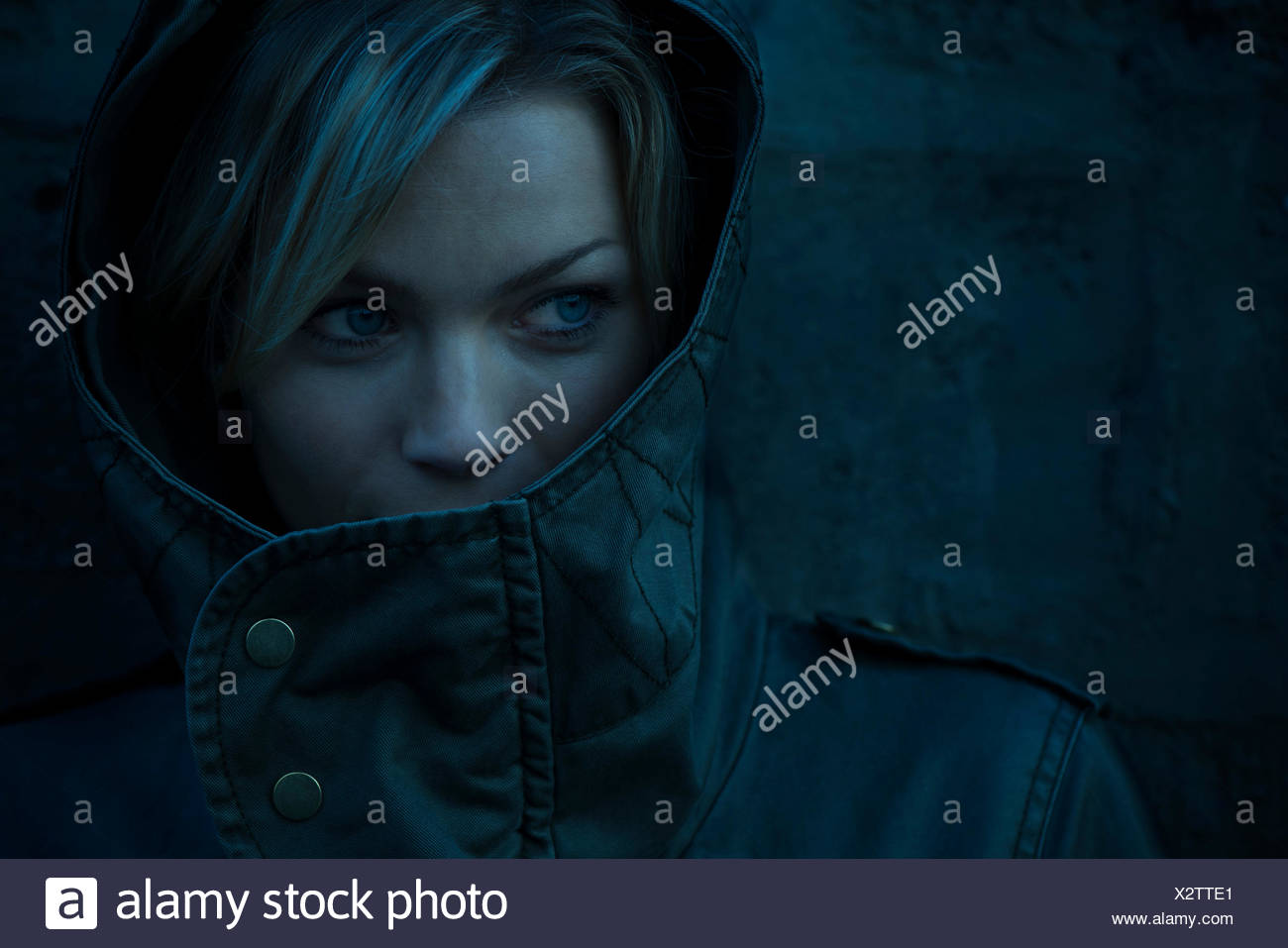Woman with face partially concealed by hood - Stock Image