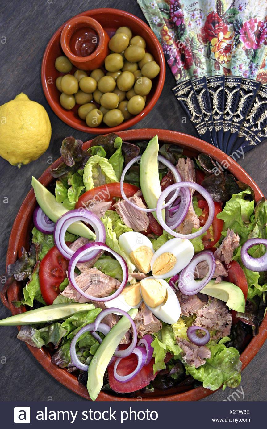 Ceramic bowl, tuna salad, olives, Spanish fan, - Stock Image