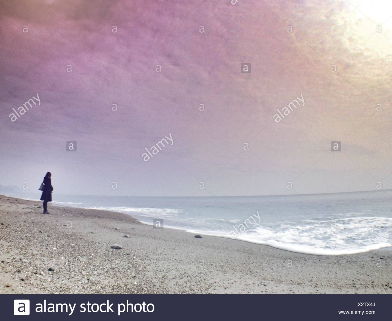 Woman Standing On Beach In Front Of Sea Against Sky During Sunset - Stock Image