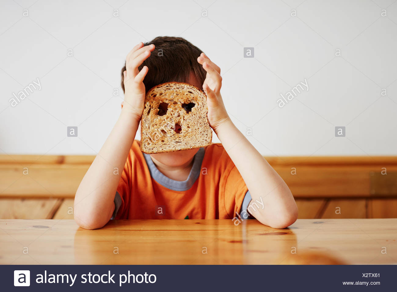 Young boy covering face with toast - Stock Image