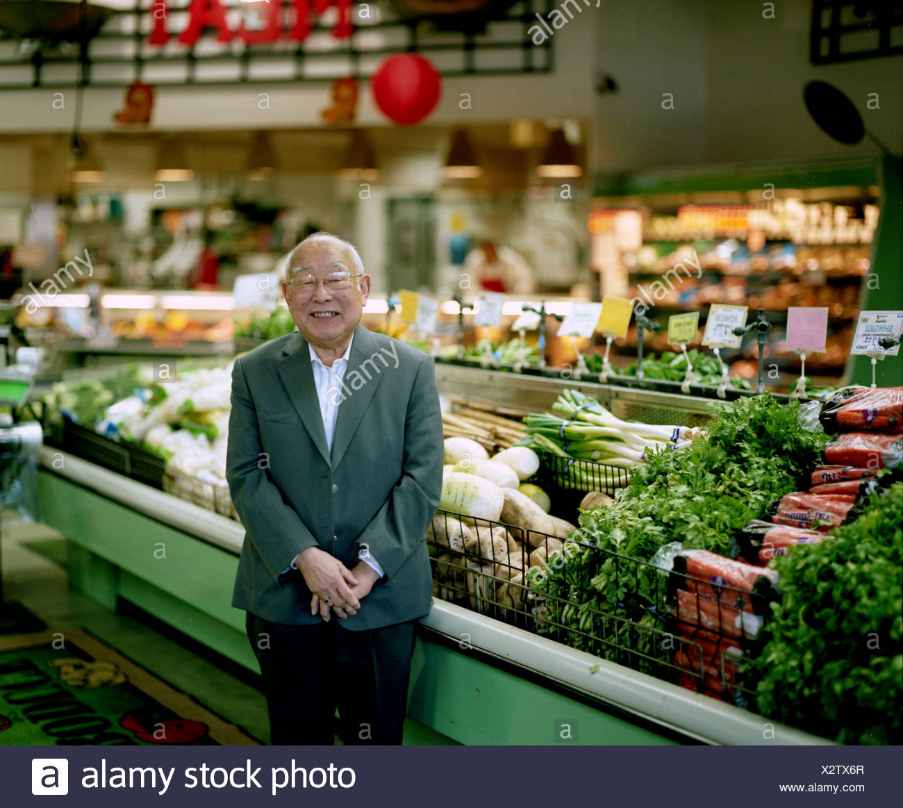 A portrait of an owner of a large grocery store standing in an aisle looking at the camera. - Stock Image