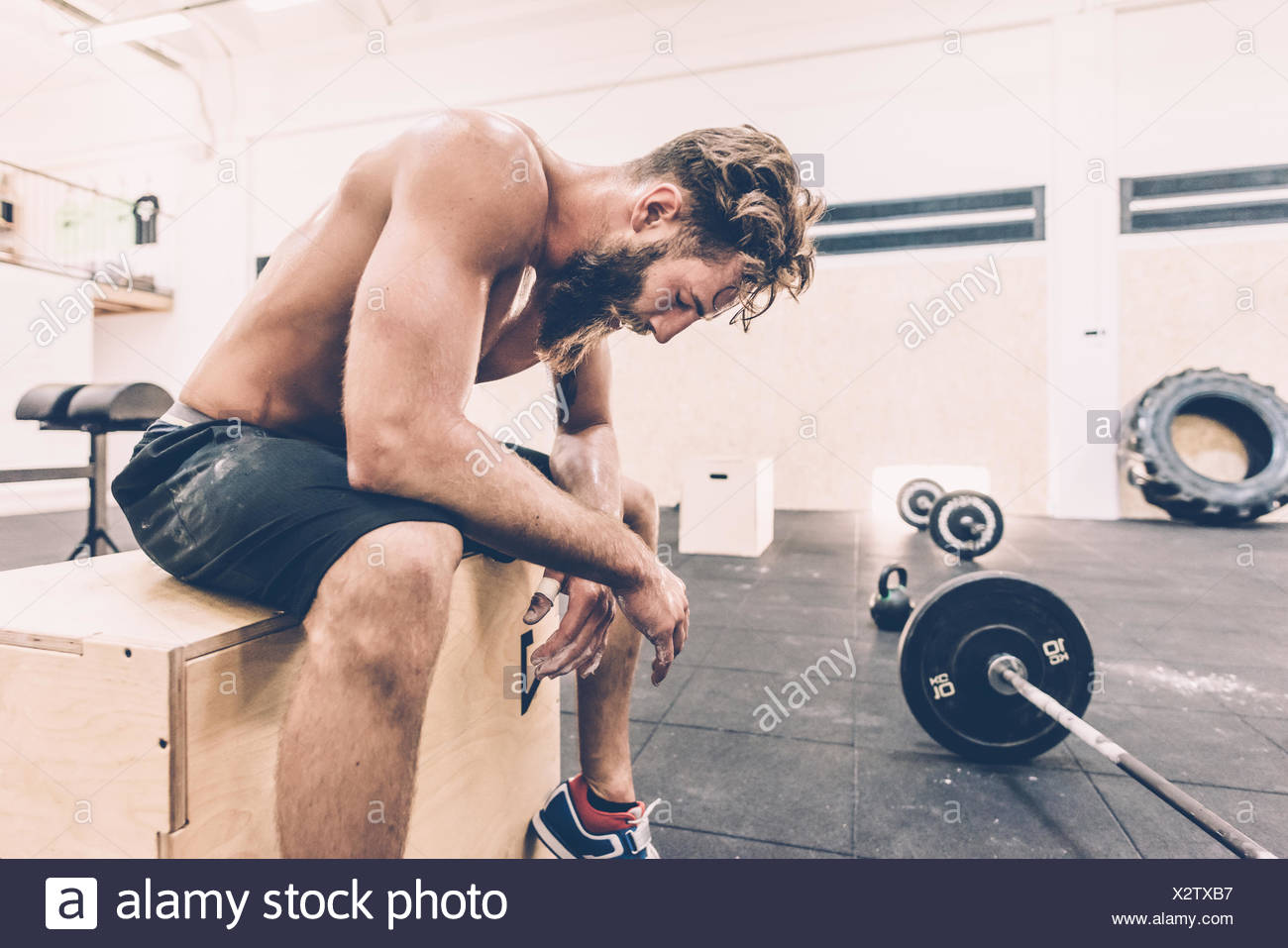 Exhausted male cross trainer taking a break from weightlifting in gym Stock Photo