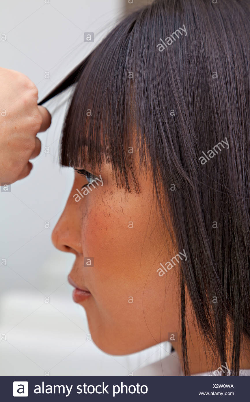 Side view of Asian woman getting a new haircut Stock Photo