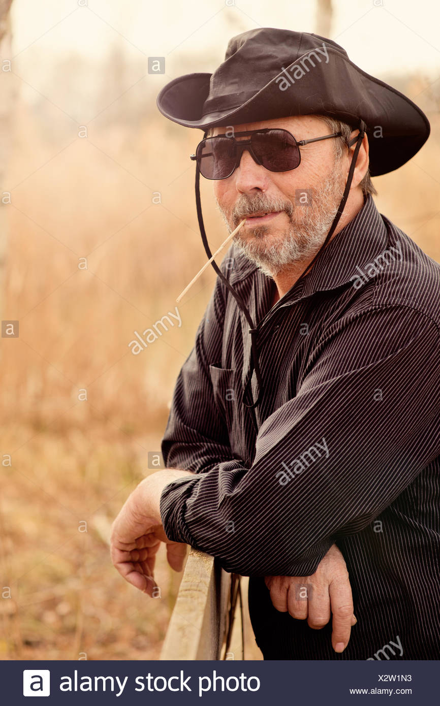 Portrait of senior man wearing sunglasses and cowboy hat - Stock Image