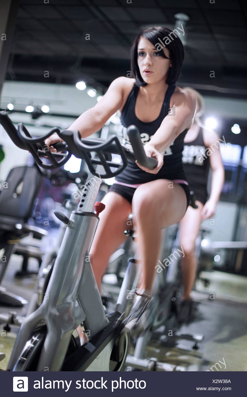 A young woman rides a stationary bike in a fitness gym.  Head in focus and legs motion blurred. Stock Photo