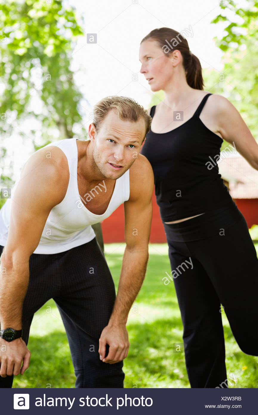 Woman exercising while leaning on tired man Stock Photo